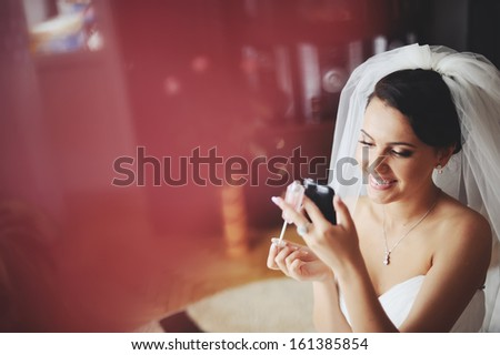 Young brunette bride having make up in the morning at home.