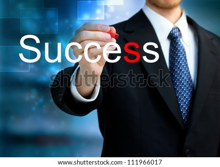 Young business man writing the word Success with red pen