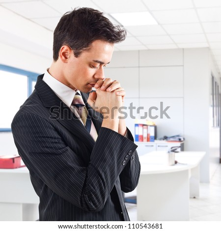 Young businessman praying in an office environment