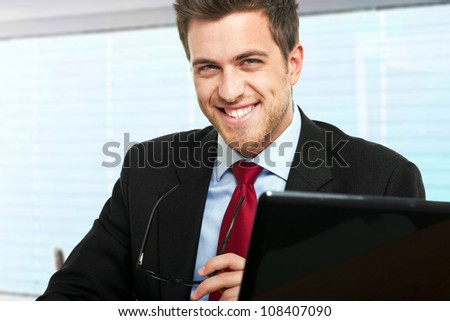 Young businessman smiling at his desk in a modern office