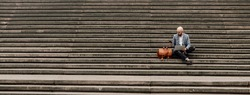 young businessman with laptop sitting on stairs ramp