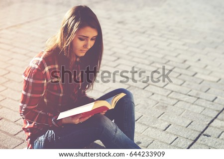 Young casual dressed hipster girl relaxing outdoors while read an absorbing novel. Female student enjoying interesting literature poem while sitting in urban setting in sunny day. Copy space area