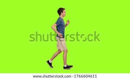 Photo of   Young caucasian man in shorts and blue t-shirt jogging on green chroma key background, Side view
