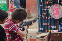 young children play with a firearm in the middle of a fair in Colombia