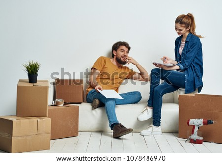 young couple sitting on the couch, moving boxes                              #1078486970
