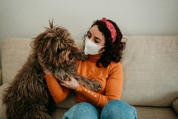 Young covid19 infected woman spending time with her faithful spanish water dog during quarantine at home. Stay home. Pandemic.