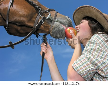 young cowgirl and her friend eating an apple, low angle view