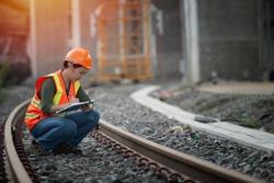 ํํYoung engineer sitting on railway inspection. construction worker on railways. Engineer work on railway