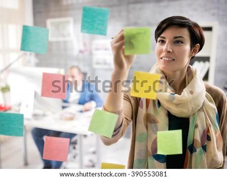 Young female designer in design studio make sketch on memo stickers