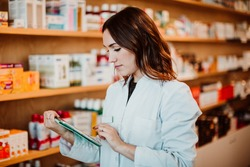 Young female pharmacist working in her large pharmacy. Placing medications, taking inventory with her tablet. Lifestyle