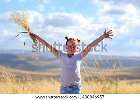 Young girl in a field celebrating Shavuot the summer harvest festival. Nature beauty, blue sky, white clouds and field of wheat. stock photo