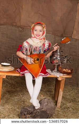 young girl in Russian national suit playing a stringed instrument
