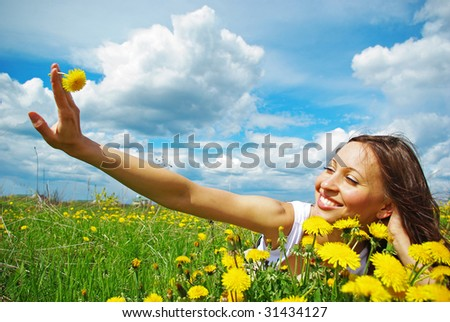 Young girl relaxing on a meadow, holding dandelion
