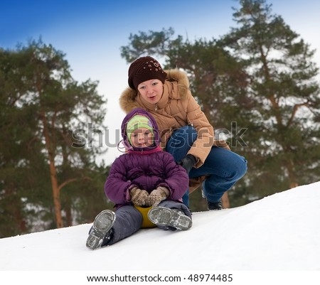 Young girl riding in a city park with a snow slide.