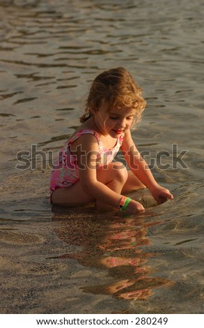 """Young girl sitting in the water on the beach, Big Island, Hawaii, (Keith Levit)"""