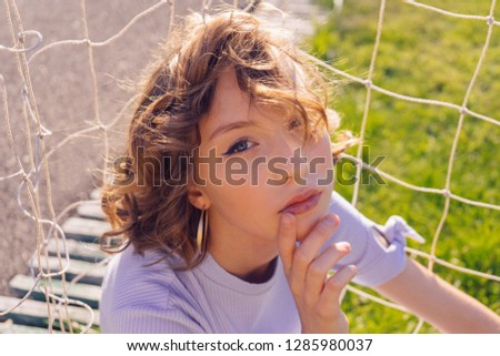 young girl sitting near the football goal in a purple suit #1285980037