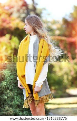 А young girl with luxurious wavy blond hair in a reversible yellow and gray scarf, white turtleneck, black short leather shorts. Autumn clothes for girls. Fashion and beauty.  Autumn concept. Сток-фото ©