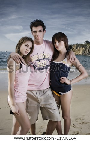 2 young girls and a guy standing on the beach