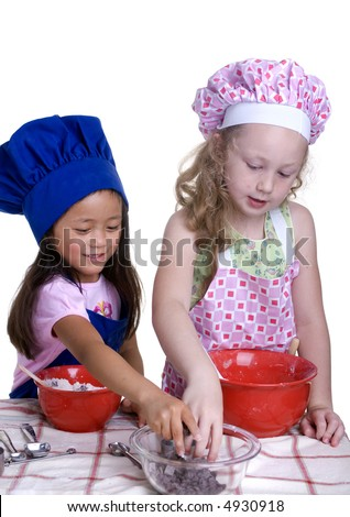 2 young girls having fun in the kitchen making a mess....I mean making something special..... Education, learning, cooking, childhood