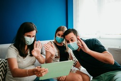 Young group of friends making a video call from home with social distance and surgical masks during the pandemic caused by the covid19