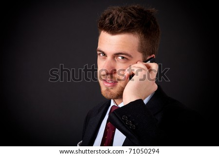Young handsome businessman on the phone against a dark background
