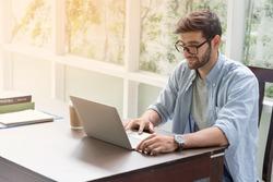 ํYoung handsome businessman using laptop at his office desk