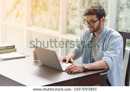 ํYoung handsome businessman using laptop at his office desk