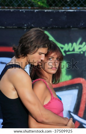 young handsome couple in front of graffiti wall
