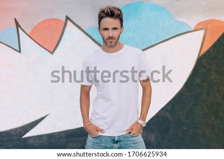 Young handsome guy is standing on a graffiti wall background. Man is wearing white, empty basic t-shirt without logo. Horizontal mock-up with light flare. Foto stock ©