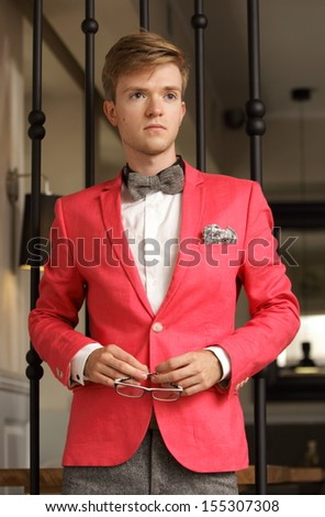 Young handsome stylish man fashion model wearing bright red jacket and bow tie posing indoor