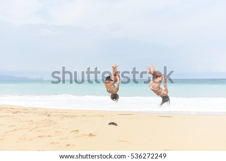 2567bf8a6 Free photos 2 Young healthy woman practicing back flips on the beach ...
