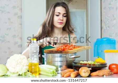 young housewife cooking with vegetables at her kitchen  at home