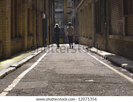 2 young lads walking down a long dark back alley