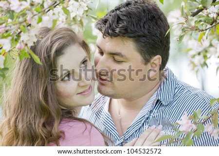 Young man and the woman against a blossoming apple-tree