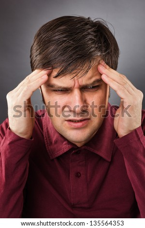 Young man having a headache isolated on gray background