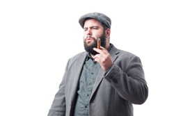 Young man in gray jacket and beret smoking a cigar isolated on white background