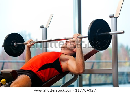 Young man lifting weights in the gym