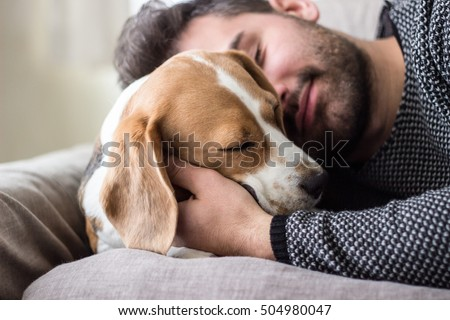 Young man sleeping with a dog  #504980047