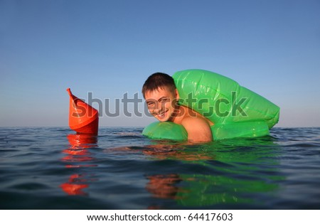 young man swims in sea on green lifeline. orange anchor buoy floats on sea.