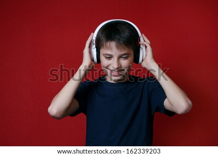 young man teen listening to music on headphones red background