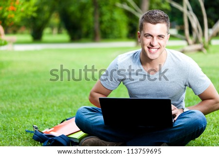 Young man using his laptop on the grass