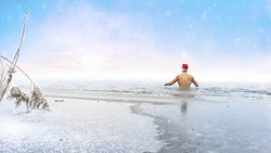 Young man with a christmas hat goes ice swimming in a lake at beautiful sunset