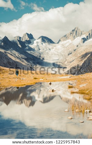 Young man with a tourist suit looking beautiful panorama nature in the mountains, the miracle of nature. Mountain Pass in Switzerland. Autumn mood at sunset. #1225957843