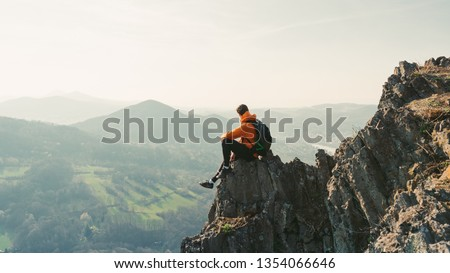 Young man with backpack sitting on rock looking into the landscape. Listening to the silence. Beautiful moment the miracle of nature.