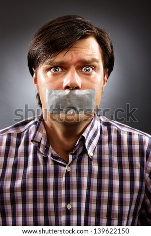 Young man with duct tape over his mouth against gray background. Conceptual image