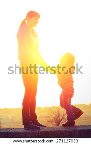 Young mother and son holding hands and laughing standing on the parapet on the background of the backlight. Family Vintage composition