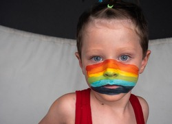 YOUNG PERSON WITH PAINTED FACE OF Pride Day Flag and LGBTIQ + pride symbol in the form of rainbow stripes painted with paints. Day against discrimination. Freedom and Equality Day