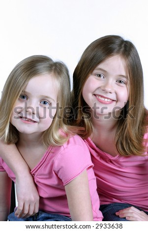2 young pretty sisters smiling on white background - stock photo