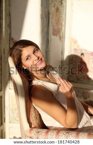 Young smiling woman sitting in vintage chair in the bedroom in the morning - Shutterstock ID 181740428