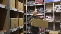 young warehouse asian woman worker in uniform holding cardboard box while doing shipping and deliveries in stockroom.
